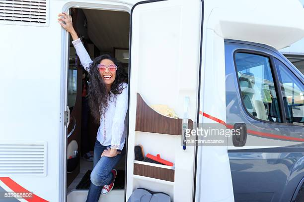 Smiling young woman showing at the camper's door
