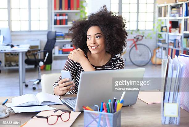Smiling young woman sitting at workplace