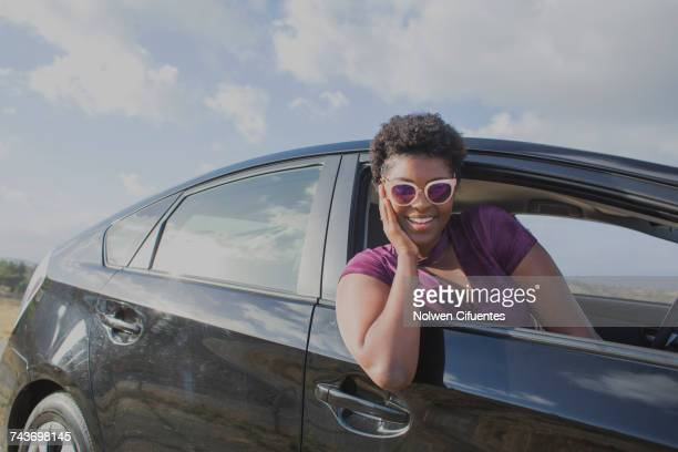 Smiling young woman sitting in car against sky