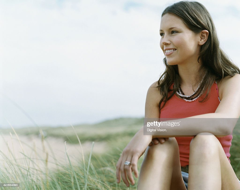 Smiling young Woman Sitting in Dune Grass