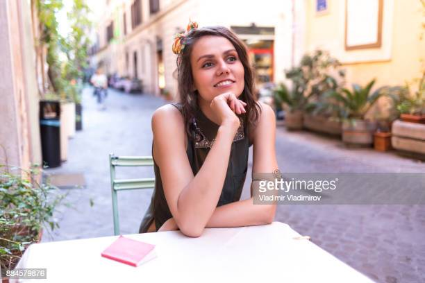 Smiling young woman sitting in sidewalk cafe in Rome