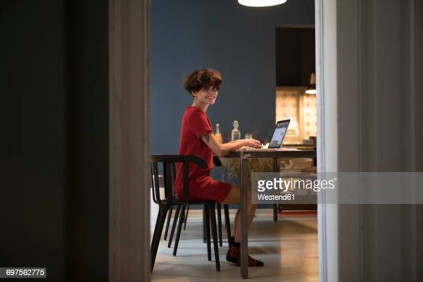 Smiling young woman sitting in the kitchen using laptop
