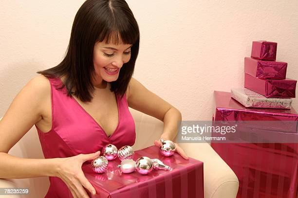 smiling young woman sitting on arm chair holding christmas present
