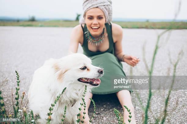 Jeune femme souriante assis sur route de campagne