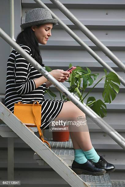 Smiling young woman sitting on stairs looking at her smartphone