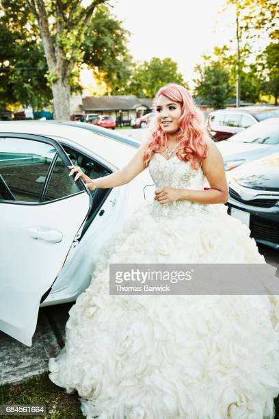 Smiling young woman standing by car in quinceanera gown