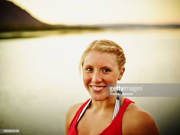 Smiling young woman standing by river at sunset