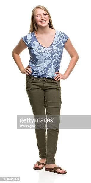Souriante jeune femme debout avec Poings sur les hanches