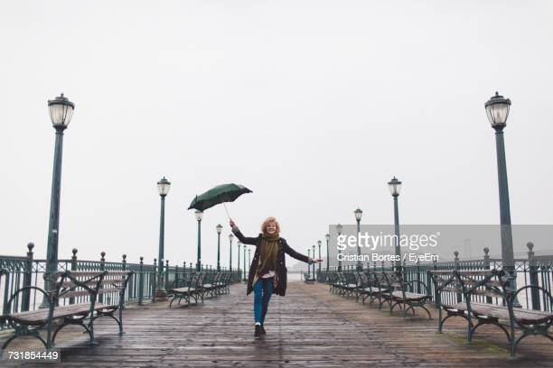 Smiling Young Woman Standing With Umbrella On Pier Over Sea