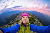 Smiling young woman takes a selfie  on  the  top of   mount Great Sivulja  ,Carpathian ,Ukraine