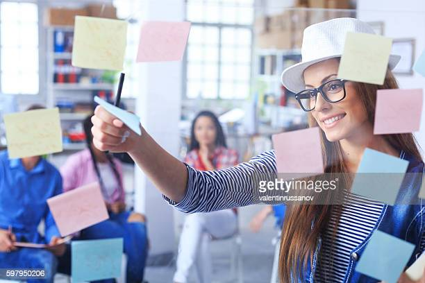 Smiling young woman taking off sticky notes