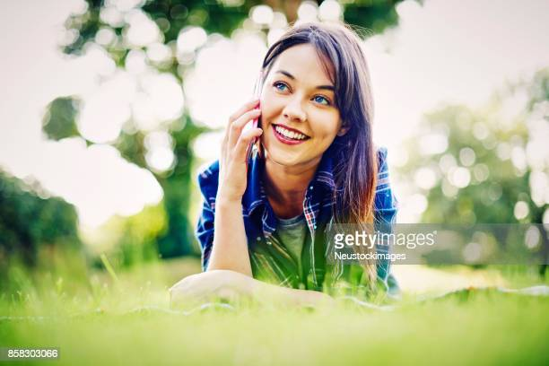 Smiling young woman talking on smart phone in park