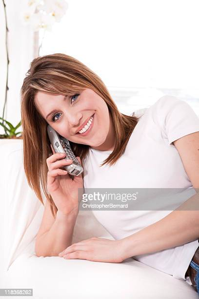 Sorridente Jovem mulher a falar ao telefone