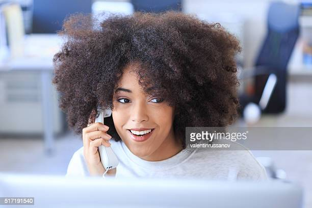 Smiling young woman talking on the telephone