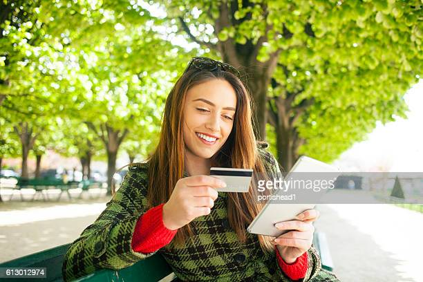 Smiling young woman using credit card for online shopping