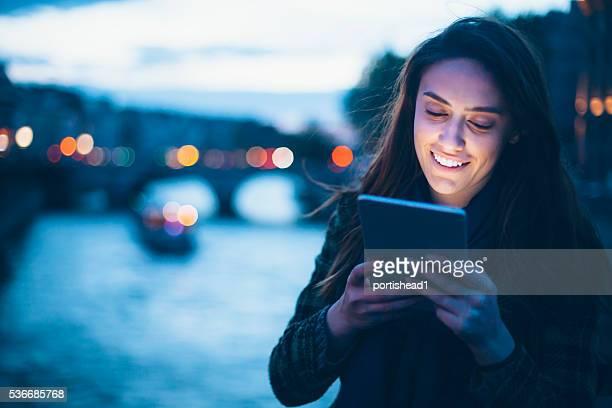 Jeune femme souriante à l'aide de tablette numérique sur le pont la nuit