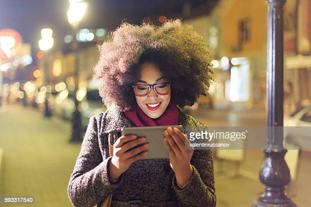 Smiling young woman using digital tablet on streets by night