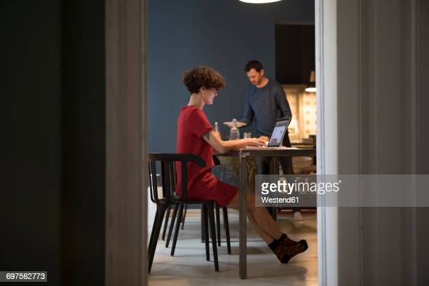 Smiling young woman using laptop in the kitchen while her partner laying the table
