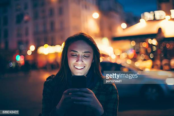 Jeune femme souriante à l'aide de smartphone dans la rue par nuit