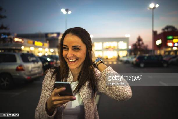 Smiling young woman using smart phone on streets by night