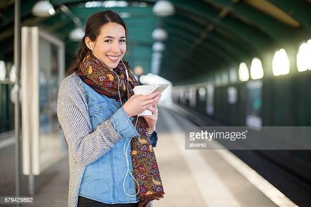 Smiling young woman waiting at subway station