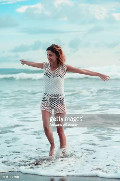 Lächelnde junge Frau zu Fuß in das Meer am Strand