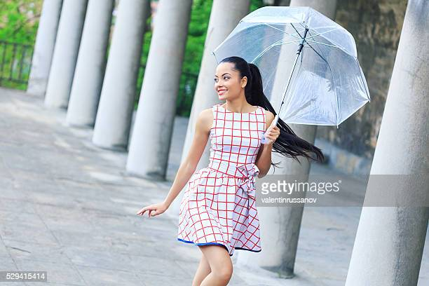 Smiling young woman walking under the rain