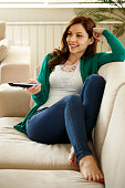smiling young woman watching tv at