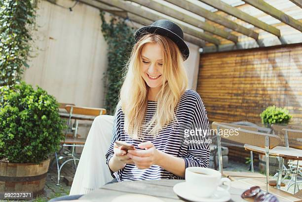 Smiling young woman wearing hat using phone while having coffee at cafe