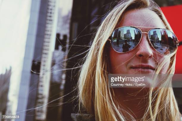 Smiling Young Woman Wearing Sunglasses Standing Against Building In City