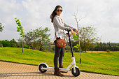 A smiling young woman with an electric scooter in the park