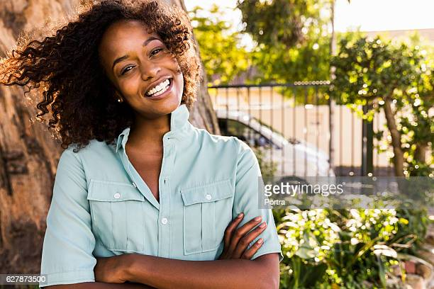 Smiling young woman with arms crossed against tree