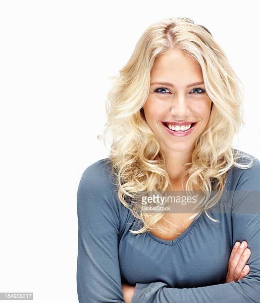 Lächelnde Junge Frau mit Arme verschränkt gegen Weiß