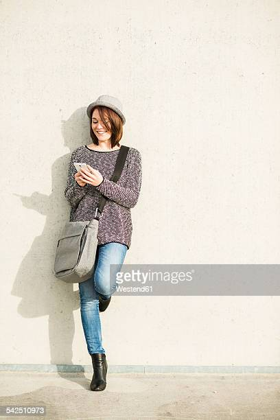 Smiling young woman with bag and cell phone