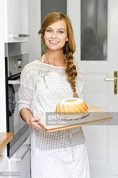 Smiling young woman with cake in kitchen