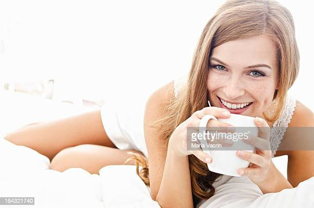 Smiling young woman with cup in bed