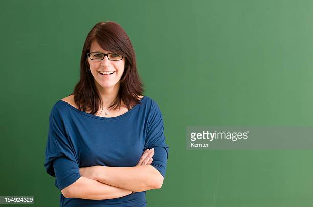 Smiling young woman with glasses in front of blackboard