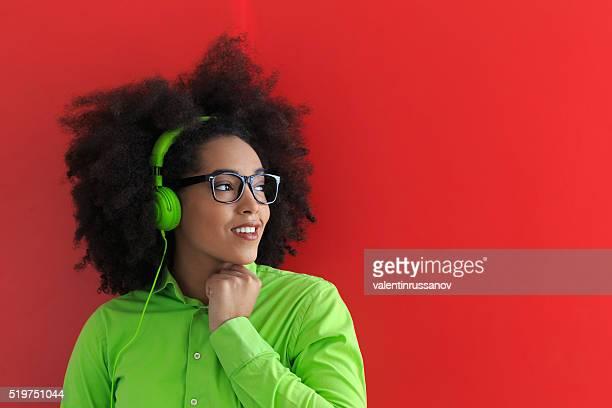 Souriante jeune femme avec un casque d'écoute de la musique vert