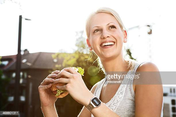 Smiling young woman with hamburger