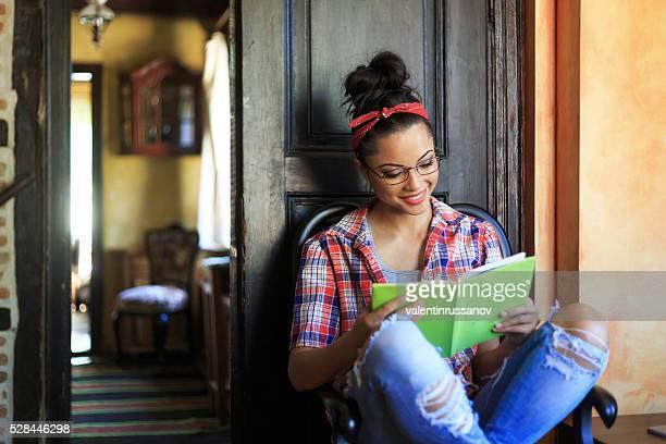 Lächelnde Junge Frau mit Stirnband beim Buchlesen