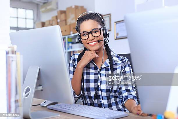 Smiling young woman with headset sitting on workplace