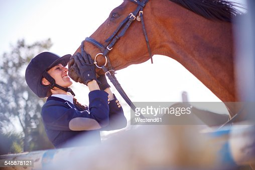 Smiling young woman with horse on show jumping course