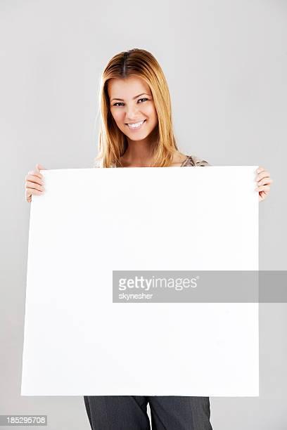 Sonriente mujer joven con cartel una pizarra acrílica.