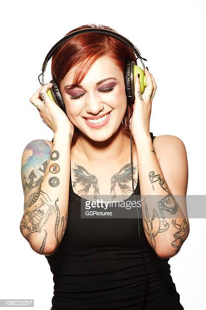 Smiling Young Woman with Tattoos Listening to Headphones