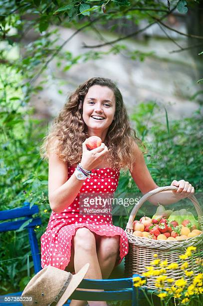 Smiling young woman with with wire basket of different fruits in a garden