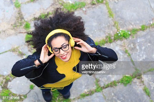 Smiling young woman with yellow headphones listening music