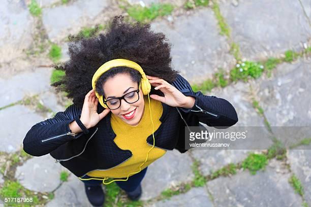 Souriante jeune femme avec un casque d'écoute de la musique jaune