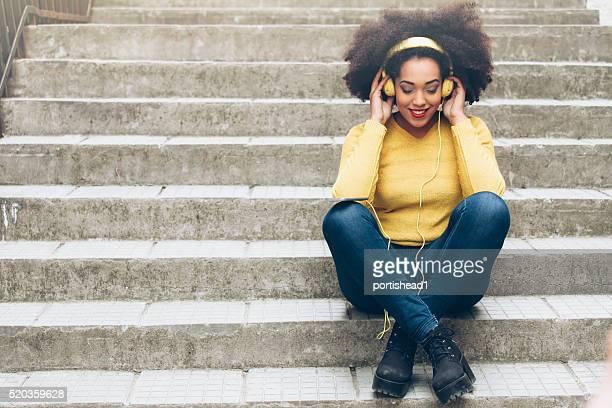 Sorridente giovane donna con cuffie seduto sulle scale giallo