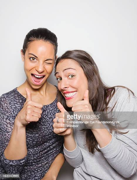 Smiling young women giving the thumbs up