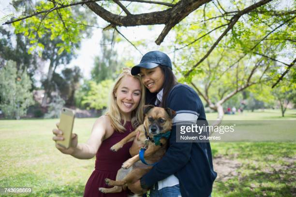 Smiling young women taking selfie with dog at park